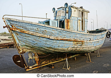 Deserted rusty old and broken wooden boat on the coast of a ocean Costa de la Luz in port Spain