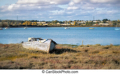 Abandoned wooden boat on the shore of the river