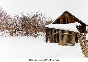 abandoned wooden shed in snow-covered village