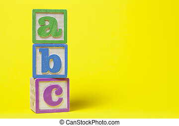 ABC Alphabet blocks stacked up on yellow background