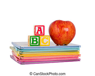 ABC Blocks and a Red Apple arranged on a stack of rainbow colored children's books. Isolated on white.