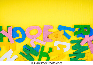 ABC wooden letters alphabet scattered on a yellow background.