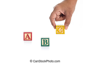 """ABC"" write in colorful wood alphabet blocks and hand holding ""C"" isolated on white"
