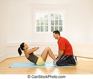 Abdominal exercise - Man holding woman\'s feet down as she...