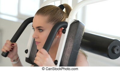 Beautiful young woman using abdominal machine at gym