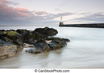 Sunrise at the entrance to Aberdeen harbour, Scotland.