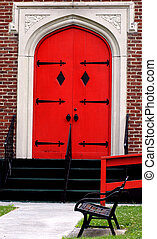 Ablaze - Old church as fire engine red door. Park bench sits...