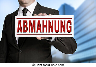 abmahnung (in german warning) sign is held by businessman
