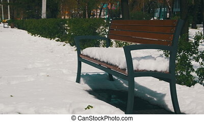 Abnormal weather in April. A Bench Covered with Snow in a...