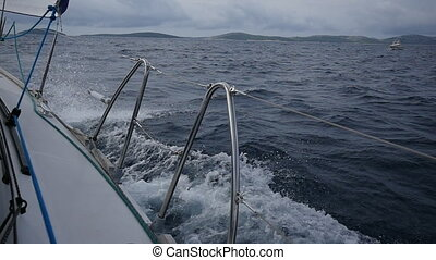 Aboard and handrails yacht on a background of sea waves in Greece.