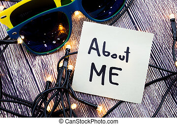 About me A motivational concept on a note paper. Two sunglasses of discrete colors with wooden background with lights. A call to stand against sexual harassment, assault and violence toward women