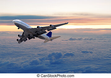 Big passenger airplane flying above the clouds and sunset