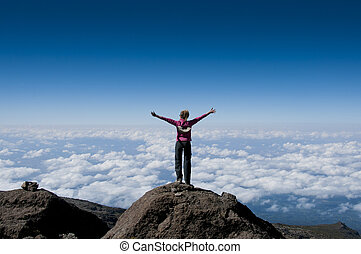 Above the clouds on Kilimanjaro - A happy trekker above the ...