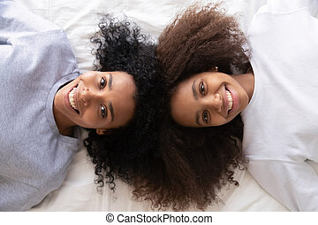Above view african daughter and mother lying on bed