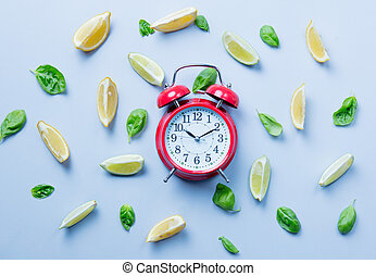 Above view at cutted lemons and limes and alarm clock on grey background