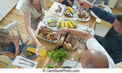 Above view of american family serving food sitting at table in home interior.