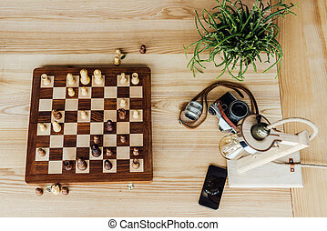 Above view of chess board set with old vintage camera on wooden table
