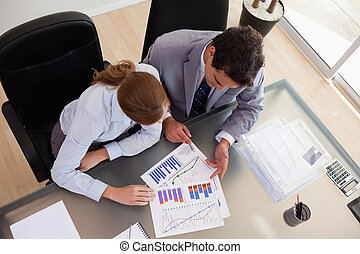 Above view of consultant analyzing data with her client -...