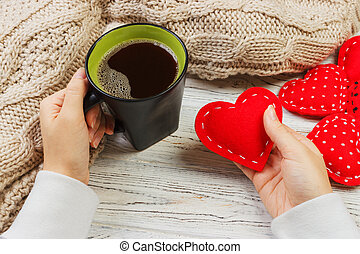 Above view of female hand holding hot cup of coffee with red heart on wood table. Photo in vintage color image style