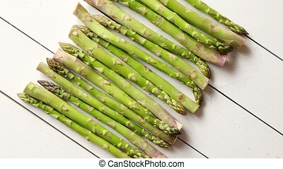 Above view of flat-lay organic raw uncooked green asparagus placed on rustic wooden table background, Close up.
