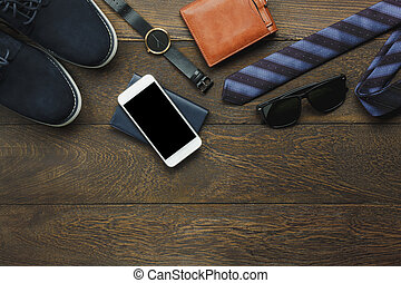Above view of items to travel with technology background concept. Essential mix variety object on modern rustic brown wood office desk. Accessories traveler teenage or adult man for vacation.