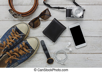 Above view of necessary items travel and technology background concept. Important accessory for travel and teenage or adult. Mix several objects on modern rustic white wooden home office desk.