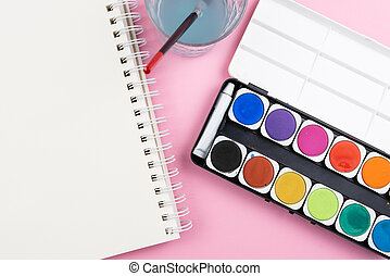 above view of watercolor paintbox, paint brush, sketchbook and glass of water on pink background