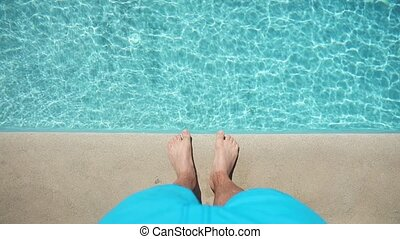 Above view on male foots near pool. Summertime vacation