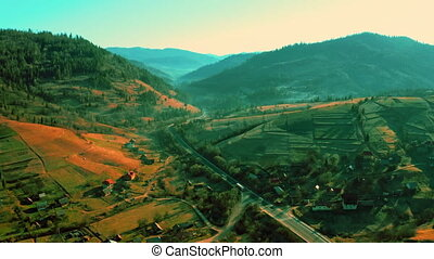 aerial cinematic view drone flies from up to down mountains landscape with green coniferous forest village in highlands