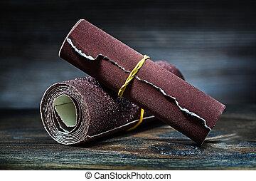abrasive sandpaper rolled up on vintage wood