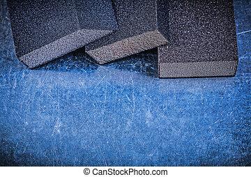 Abrasive sponges on scratched metallic background construction c