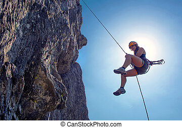 Abseiling woman - Young, tough, woman, abseiling from a ...