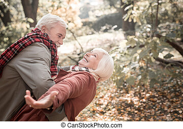 Delighted aged woman being held by her husband