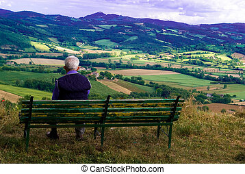 An old man enjoyes in contemplation the beautiful landscape in front of him, Umbria Italy