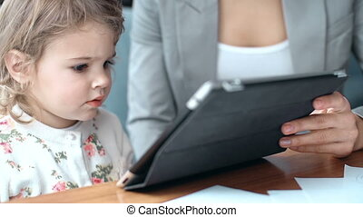 Absorbed in Device - Cropped mother teaching her child to...