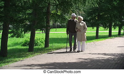 Absorbed in Each Other - Elderly couple walking together and...