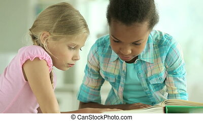 Excited girls reading an interesting book together then looking at camera