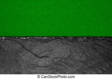Abstract background composition of divided in the half matt dark green color paper and black stone with copy space