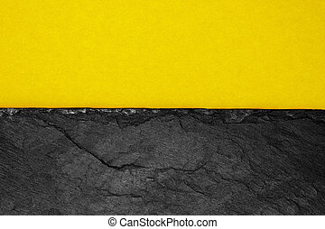 Abstract background composition of divided in the half matt dark yellow color paper and black stone with copy space