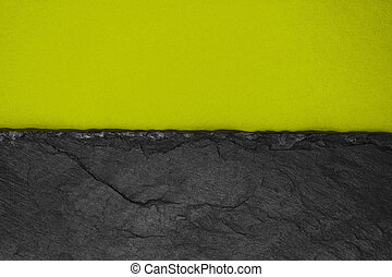 Abstract background composition of divided in the half matt dark yellowish green color paper and black stone with copy space
