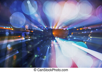 Abstract background image of circular bokeh motion blurred street light background of city, traffic light from car on street at night time. Zoom effect.
