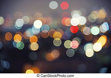 Abstract background image of circular bokeh motion blurred street light background of city, traffic light from car on street at night time.