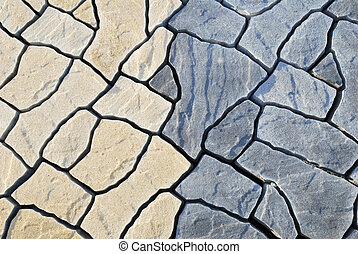 Abstract background paving consisting of irregular stones of two colors in top view