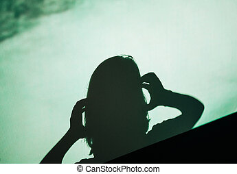 shadow silhouette of female woman screaming scared holding head with hand