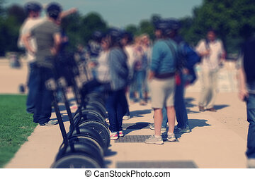 Abstract background. Tourists near the segways in the park....