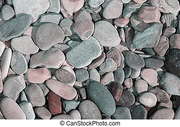 Abstract background with round peeble stones close up.