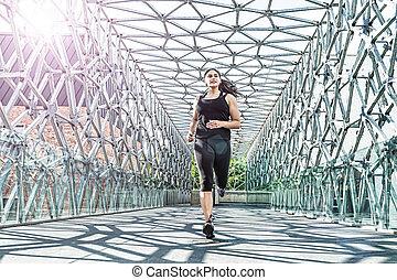 Abstract - Beautiful woman running on a modern metal bridge