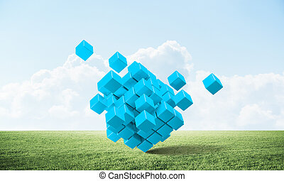 Abstract blue cubes on green meadow