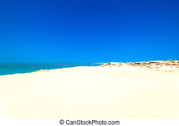Abstract Blue sea and white sand background at summer day. Sandy beach wallpaper.