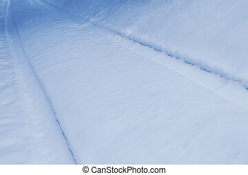 Vehicle tracks crossing the snowy winter background